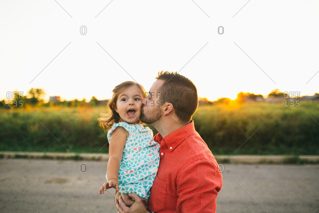 A father kisses his little girl's cheek