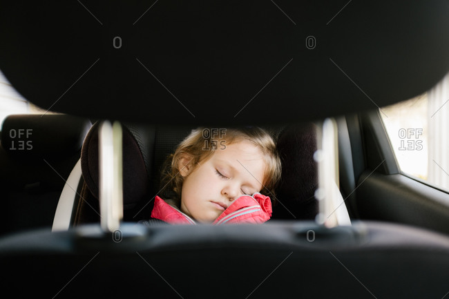 View of young girl asleep in car seat from the front seat
