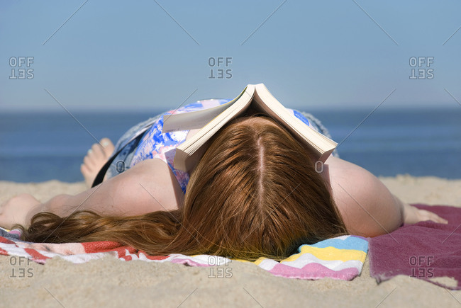 Woman lying on beach face covered by book