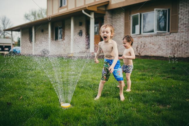 A little boy yells as a sprinkler hits him