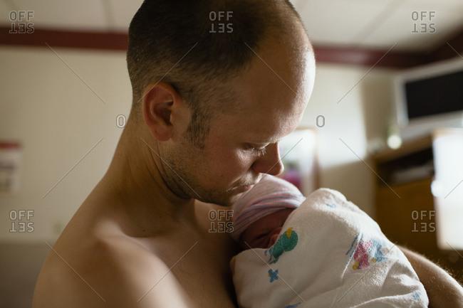 A father cradles his newborn