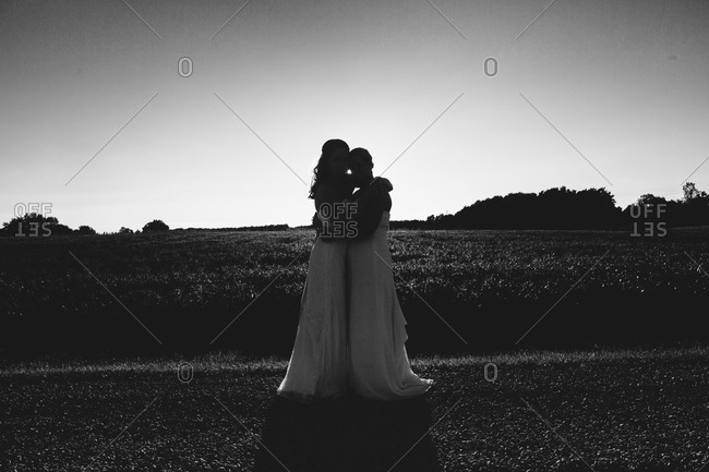 Two brides hug in a field