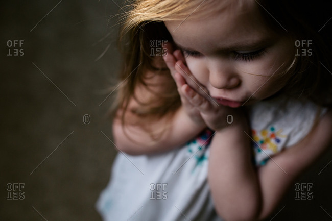 Little girl with her hands against her cheeks