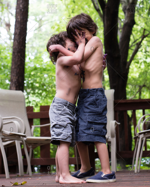 Two young boys grabbing each other and smearing one another with paint