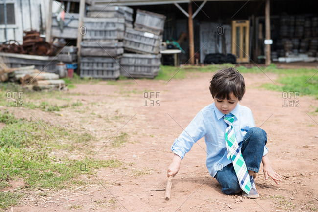Boy playing with a stick in the dirt outside a barn