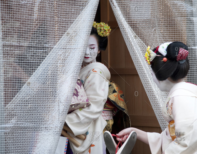 Kyoto, Japan - April 8, 2012: Two geisha enter a curtained area of a building