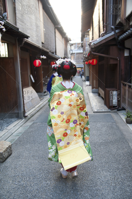 Back view of an apprentice geisha walking in a narrow alleyway in Kyoto