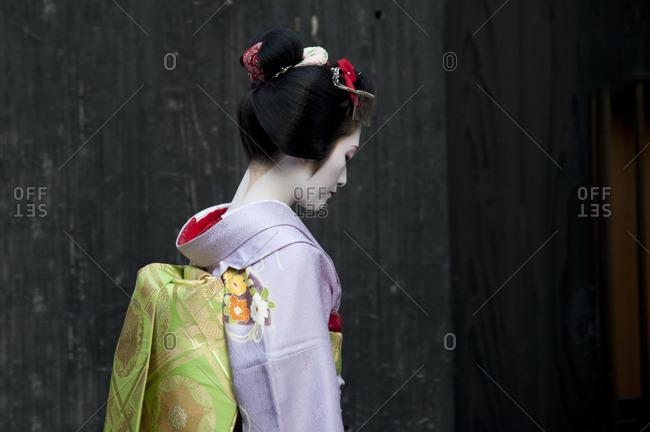 Kyoto, Japan - April 8, 2012: An apprentice geisha in profile in Kyoto