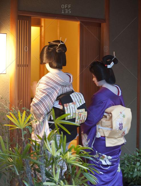 Kyoto, Japan - April 8, 2012: Two geisha enter a tea house