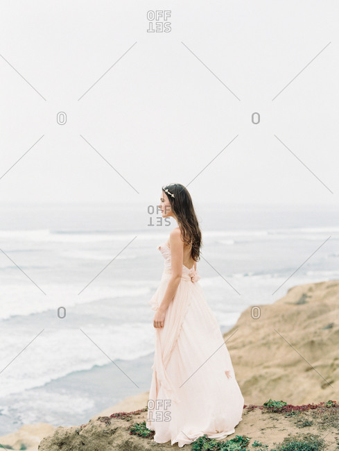 A bride stands on the edge of an ocean cliff
