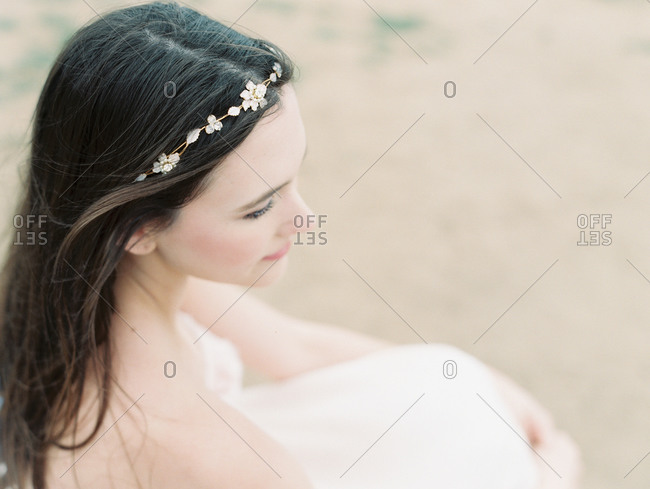 A bride sits on the beach