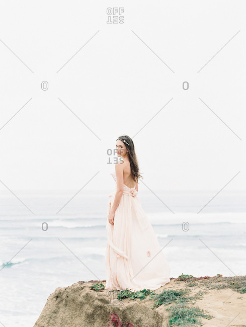 A bride standing on the edge of an ocean cliff looks over her shoulder