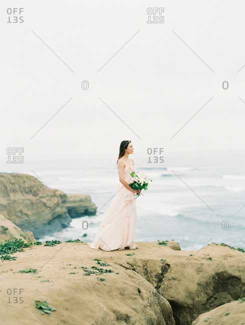 A bride looks out at the ocean