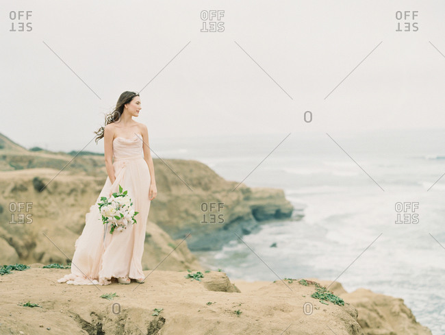 A bride holding her bouquet looks out at the ocean