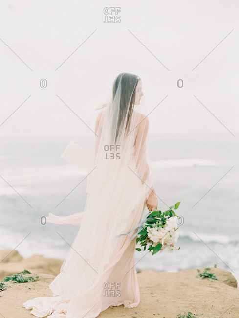A bride stands in front of the ocean