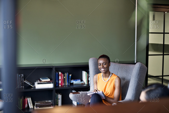 A woman smiles at a colleague in an office common area