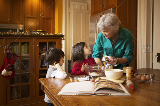 Woman and two young children making cookie dough