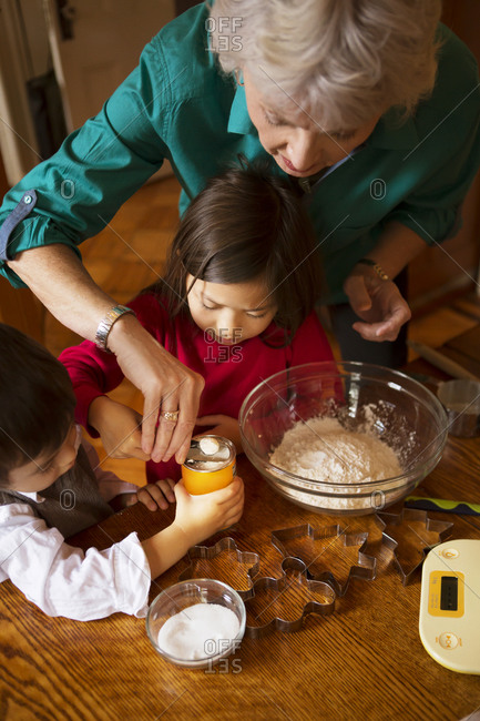 Woman and two young children mixing cookie dough