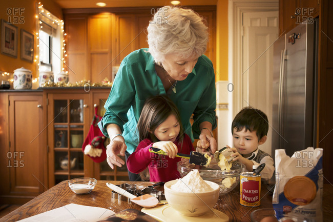 Woman and two young children mixing cookie dough ingredients