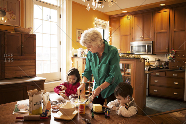 Woman and two kids mixing cookie ingredients