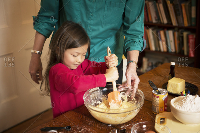 Girl stirring cookie dough with woman