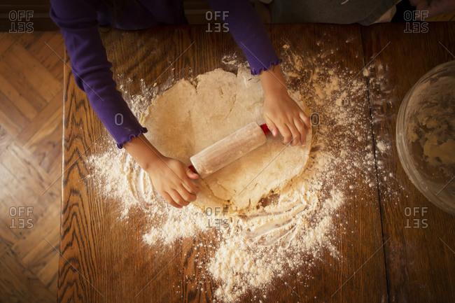 Young girl rolling out cookie dough from above