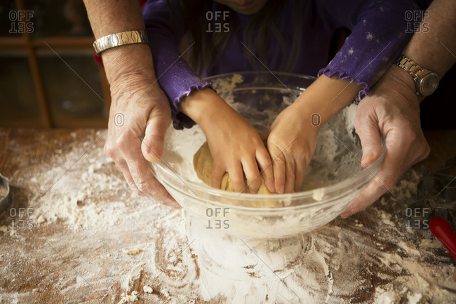 Woman helping girl knead cookie dough