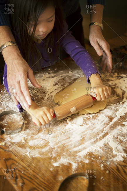 Woman helping young girl roll out cookie dough