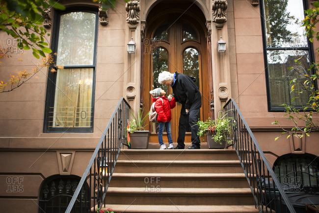 Older woman and girl saying goodbye on step