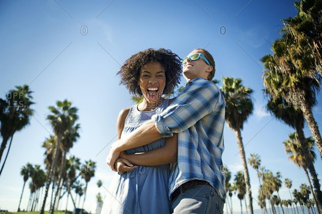 Young interracial couple embracing in tropical climate