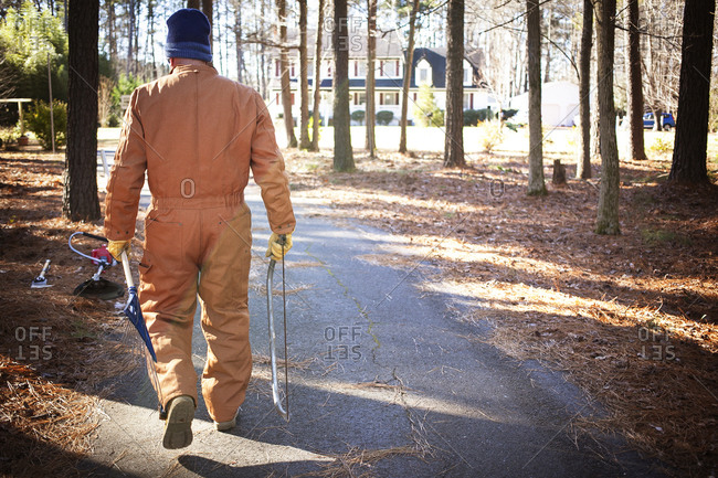 Older man in overalls carrying saw and axe