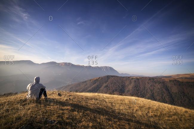 Man sitting on grassy mountain hill