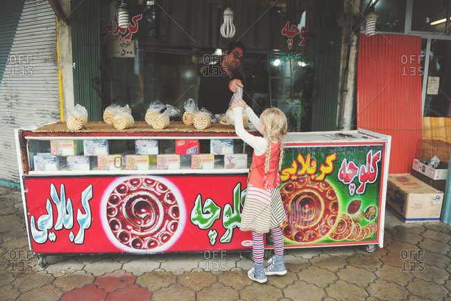 Fuman, Iran - October 26, 2014: Girl buying sweets from a vendor