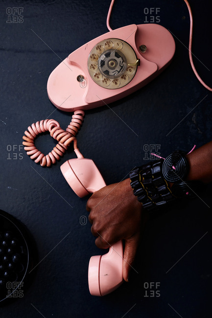 Woman's hand on rotary dial phone