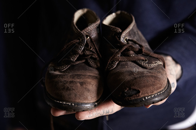 Hands holding up pair of worn old shoes