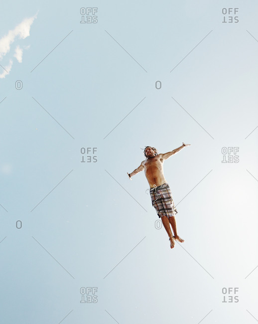 Teen doing swan dive off midair