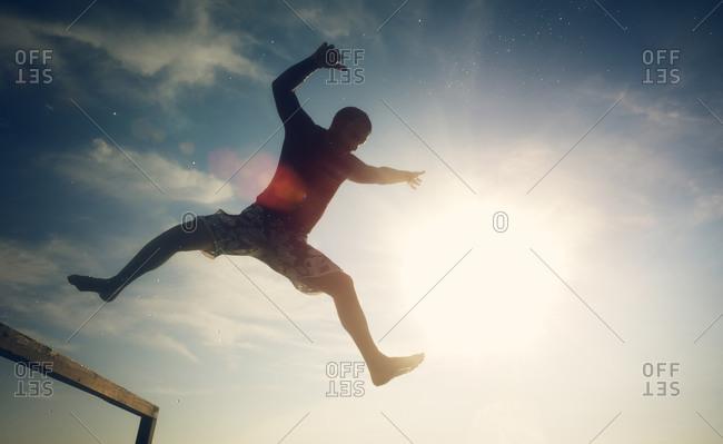 Teen boy midair jumping off pier