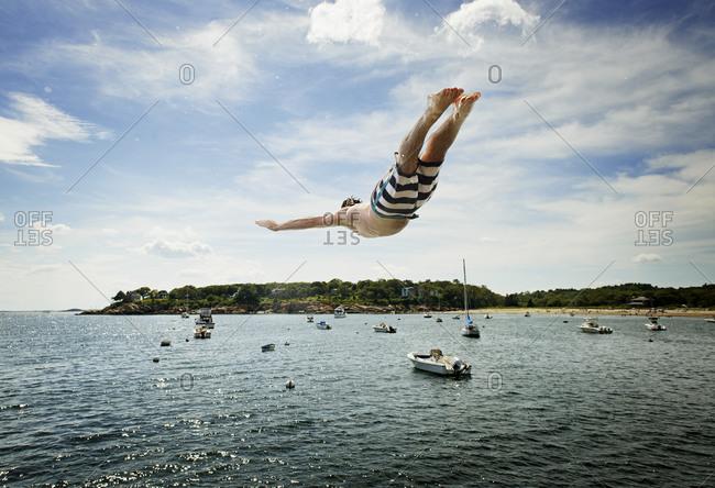 Teen boy midair diving off pier