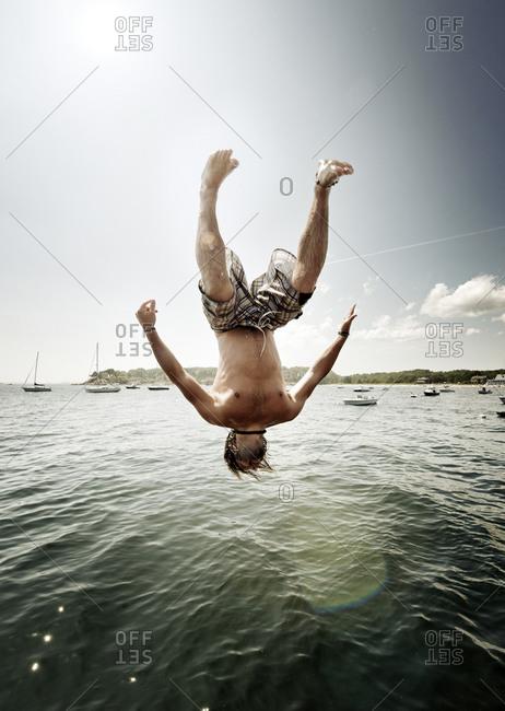 Teen boy midair flipping off pier
