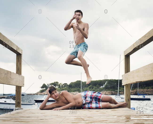 Teen jumping by friend on pier
