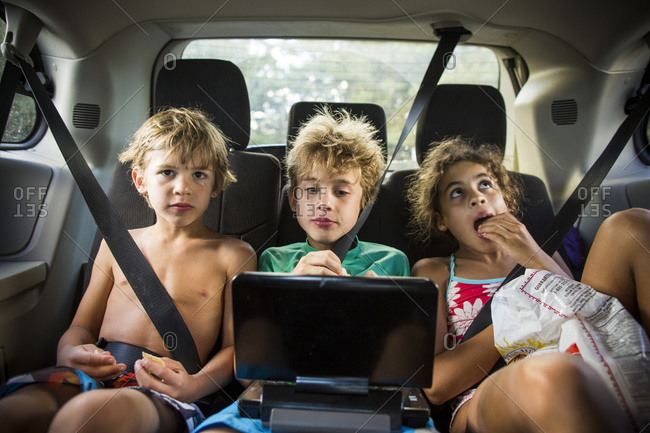 Three kids watching video riding in car