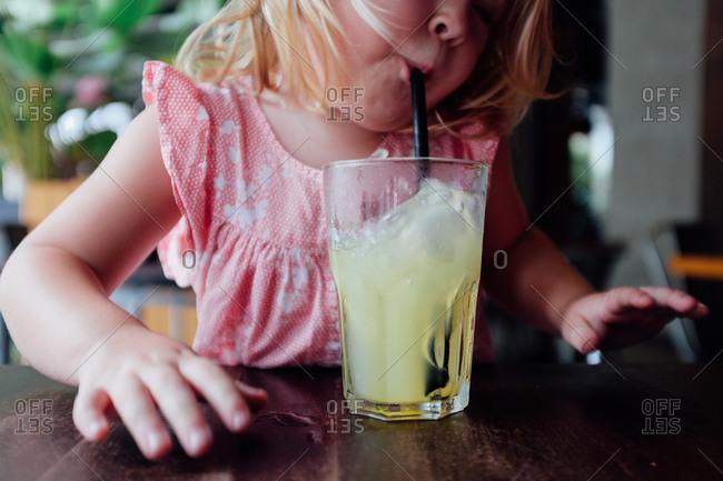 Kid making effort to drink juice through straw