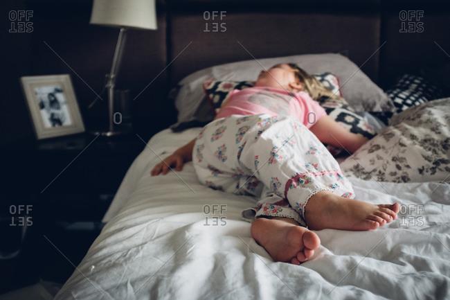 Girl sprawled out asleep on bed