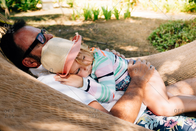 Girl and man lying together on hammock