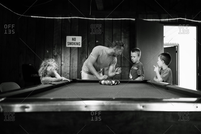 Man teaching his children how to play pool