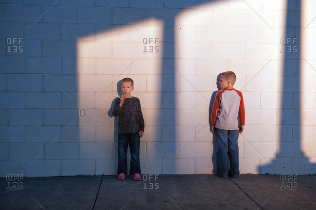 Boys standing outdoors against a cinder block wall at sunset