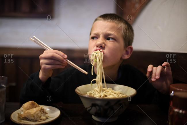 Boy struggling to eat noodles in a restaurant