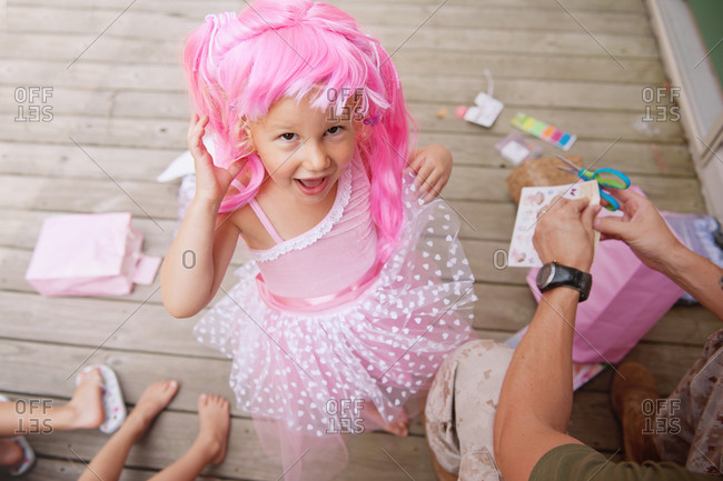 Young girl wearing a pink wig and costume outside on deck