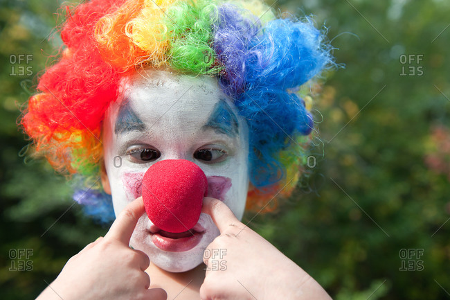 Young child wearing a clown wig, makeup and nose