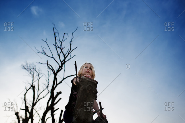 Young girl climbing on a tree trunk
